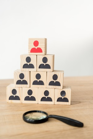 selective focus of management hierarchy pyramid near magnifier on white