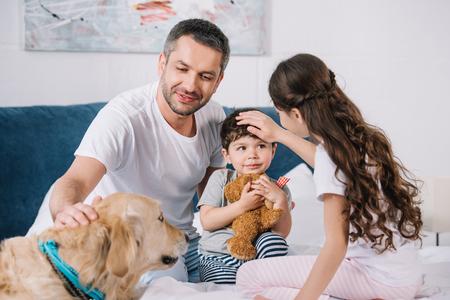 selective focus of man touching golden retriever near children at home