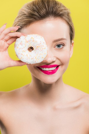 cheerful woman covering eye with tasty doughnut isolated on yellow