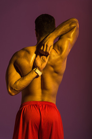 back view of sportive man with muscular torso stretching on purple background