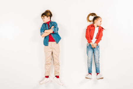 top view of displeased kid with crossed arms near friend on white