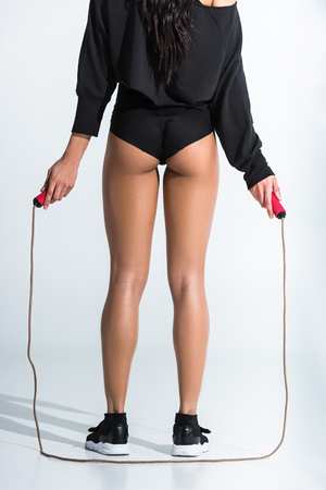 back view of athletic african american girl holding skipping rope on white Stock Photo
