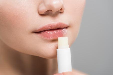 Ausgeschnittene Ansicht einer jungen Frau mit Lippenbalsam isoliert auf grau