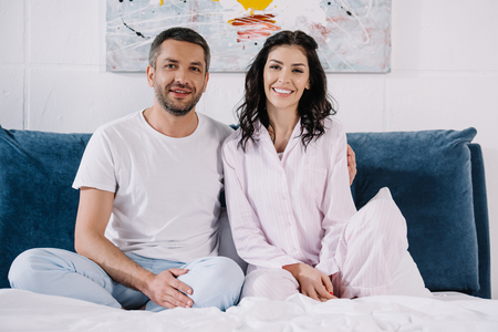 cheerful man sitting near happy woman and smiling on bed Standard-Bild - 122866211