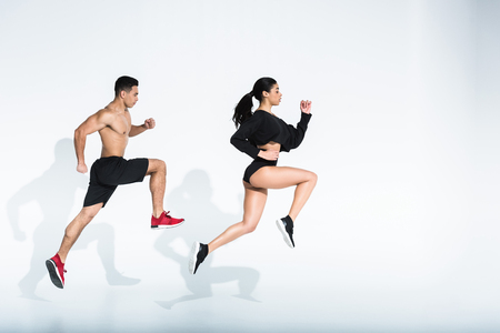 side view of sportive african american girl and athletic mixed race man running on white background
