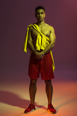 handsome mixed race man in red shorts, and yellow jacket tied on torso looking at camera on dark background Stock Photo