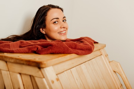 smiling woman taking steam bath in spa center