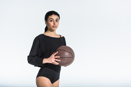 beautiful african american girl in black sportswear holding ball and looking at camera on white