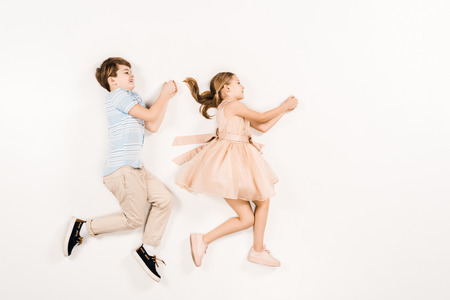 top view of cheerful kids gesturing while lying on white