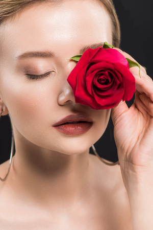 selective focus of young woman holding red rose isolated on black