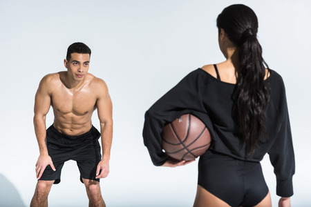 handsome mixed race man looking at sportive african american woman with ball on white