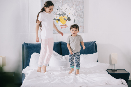 happy child jumping on bed with adorable toddler brother
