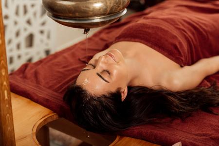 Rilassata giovane donna sdraiata sotto la nave shirodhara durante la procedura ayurvedica