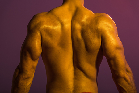 back view of shirtless athletic man with muscular torso on purple background