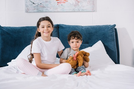 happy kid smiling while sitting with toddler brother on bed