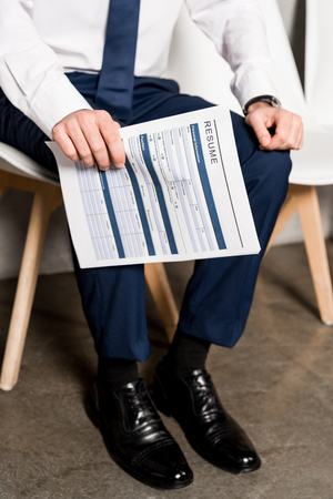 cropped view of man holding resume while sitting on chair 免版税图像