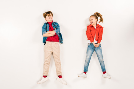 top view of cheerful kid near friend with crossed arms on white