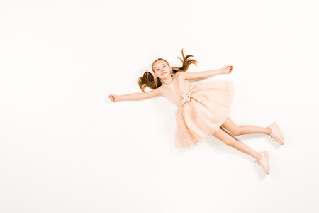 top view of smiling child in pink dress flying and looking at camera on white Standard-Bild - 122867553