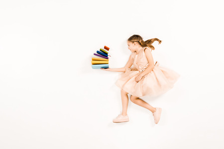 top view of cheerful kid in pink dress holding books on white