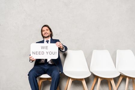 glücklicher Recruiter, der auf einem Stuhl sitzt und eine Sprechblase hält, mit der wir dich beschriften müssen