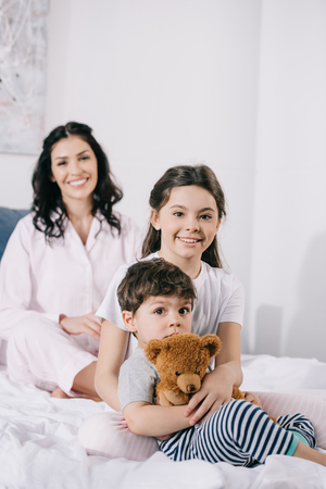 selective focus of happy kid near toddler brother and cheerful mother in bedroom