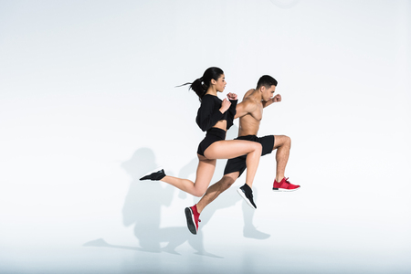 side view of sportive multicultural woman and man in sportswear and sneaker running on white background 写真素材