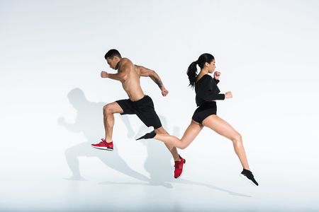 sportive african american girl and athletic mixed race man running on white background