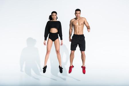 homme et femme multiculturel sportif sautant sur fond blanc