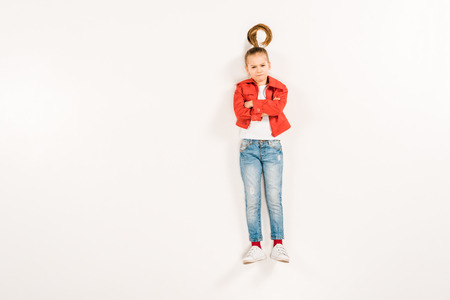 top view of displeased kid with crossed arms on white
