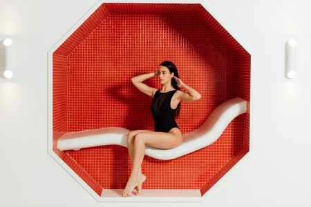 gioiosa giovane donna in costume da bagno seduta sul divano nel centro termale