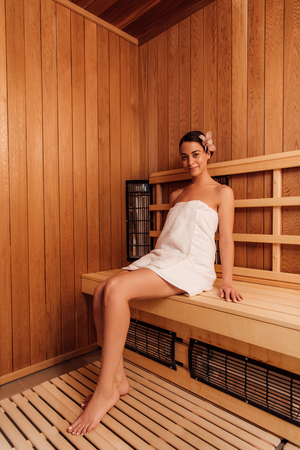 low angle view of smiling barefoot girl in towel with flower in hair in sauna