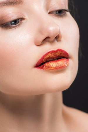 close up of attractive woman with orange lips isolated on black Imagens