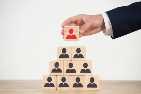 vue recadrée de l'homme parlant cube en bois de pyramide sur blanc