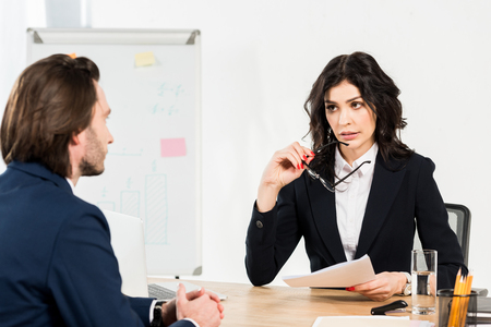 selective focus of brunette recruiter holding paper and glasses and looking at man
