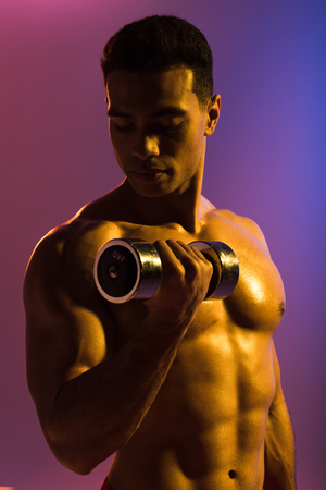 handsome sportive mixed race man training with dumbbell on purple and blue gradient background