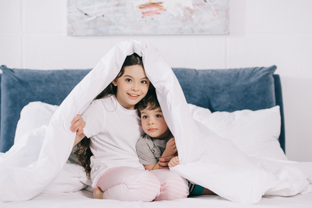 cheerful kid sitting under blanket with cute toddler brother Stockfoto
