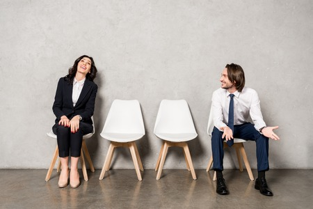 happy man looking at attractive woman smiling while sitting on chair