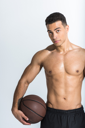 good-looking athletic mixed race man with muscular torso holding brown ball and looking at camera on white 版權商用圖片