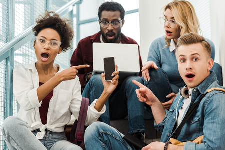 group of shocked multicultural students with laptop and smartphone in university