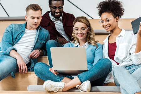 Estudiantes multiculturales sonrientes usando un portátil en la sala de conferencias