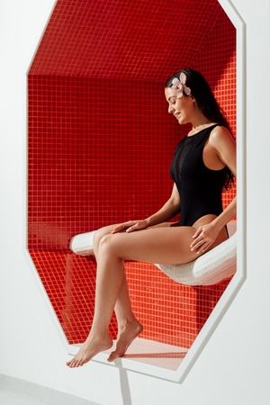 smiling young woman in swimsuit sitting on sofa in spa center 版權商用圖片