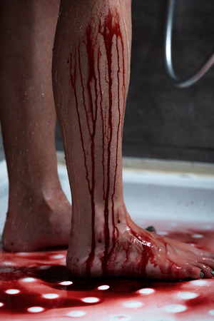 partial view of barefoot bleeding woman in bathroom 版權商用圖片