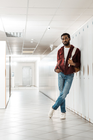 full length view of african american student with backpack in corridor in university Stock Photo