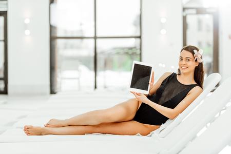 uśmiechnięta boso kobieta leżąca na leżaku i pokazująca cyfrowy tablet z pustym ekranem Zdjęcie Seryjne