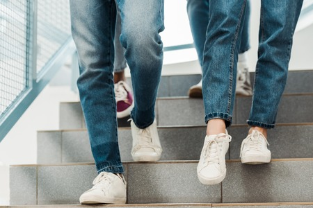 partial view of group of people in jeans on stairs Imagens