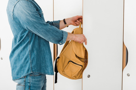 cropped view of student with backpack opening locker