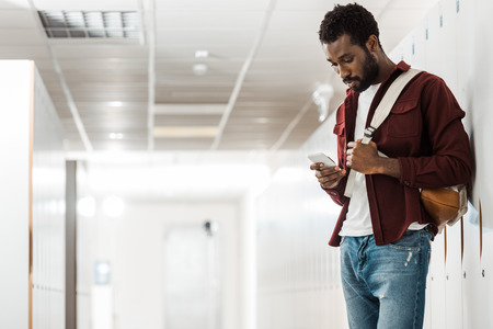 african american student with backpack using smartphone in corridor