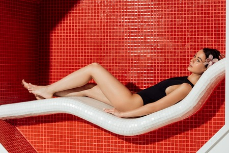 relaxed woman in swimsuit lying on sofa in spa center