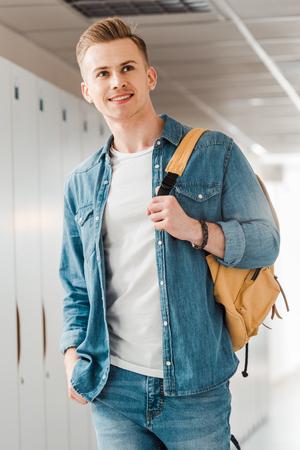 smiling student with backpack looking away in corridor in university 版權商用圖片