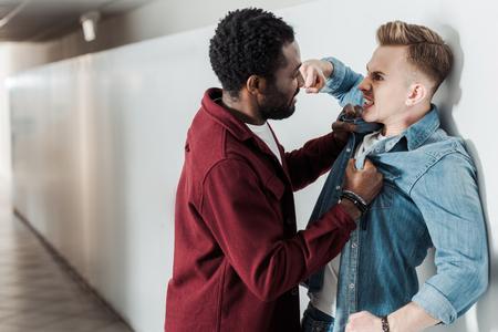 Zwei multiethnische Studenten kämpfen im Korridor im College